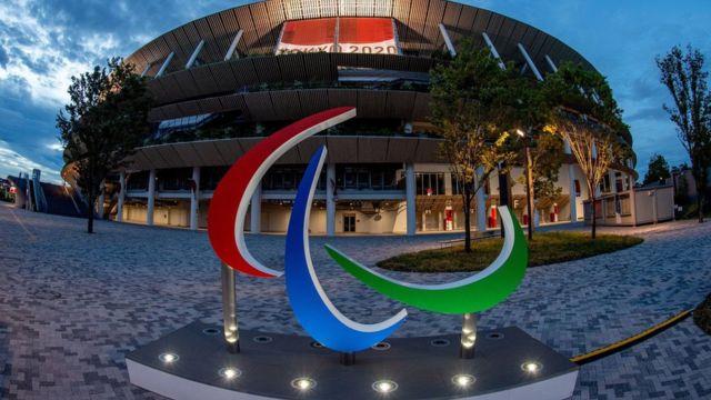 """Fotografía del estadio olímpico en Tokio, Japón por fuera, el cielo se ve un poco nublado porque está a punto de anochecer, el estadio se ve encendido con luces cálidas de color amarillo, en la entrada tiene una gran pancarta de color rojo con el texto """"Tokyo 2020"""" escrito en ella, de frente a la entrada, aparece una gran escultura del logotipo representativo de los paralímpicos, tres elementos de forma curveada de color azul, rojo y verde sobre fondo blanco."""