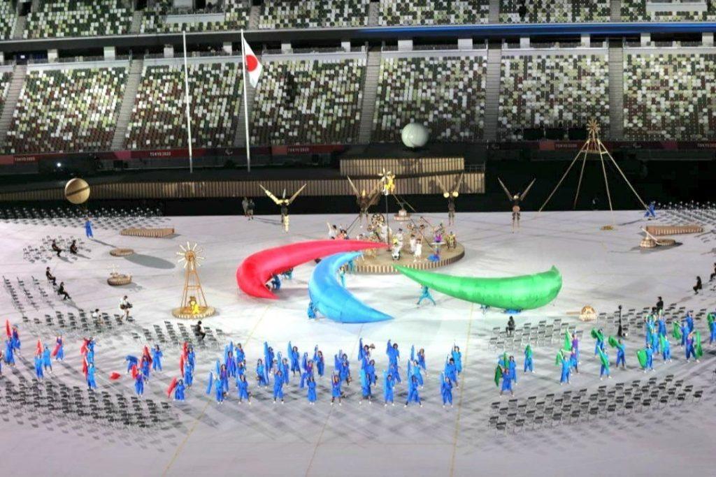 Fotografía del escenario de un gran estadio, al centro aparece un performance de personas que con tres telas de color verde, rojo y azul componen el logotipo representativo de los Juegos Paralímpicos, al rededor aparecen 57 personas vestidas de traje completo amarrado con una cinta, todo de color color azul, sostienen banderas de color rojo y verde.