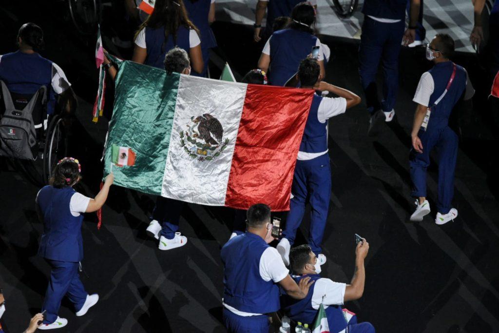 Fotografía con fondo oscuro de color negro que muestra a una parte la delegación mexicana en los Juegos Paralímpicos en donde se alcanza a apreciar a diez personas caminando, de espaldas a la cámara: entre dos personas, aparentemente dos hombres, sostienen con su brazo en la espada la bandera de México.