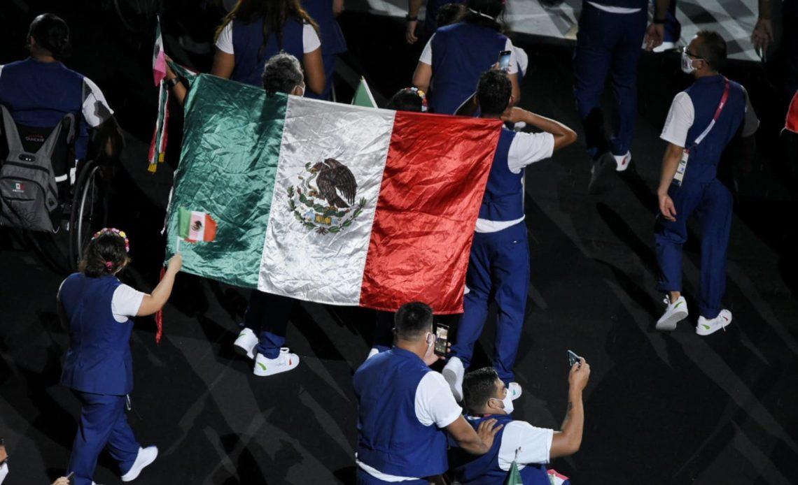 Fotografía que muestra una enorme bandera de México entre miembros de la delegación que representa al país en los Juegos Paralímpicos de Tokyo 2020. Los y las atletas que desfilan visten el uniforme azul con playera banca, y fueron captados de espaldas.
