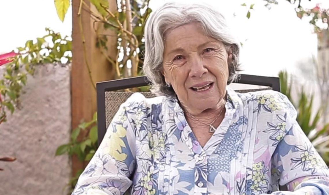 Fotografía de una mujer mayor, sentada en un espacio rodeado por plantas. Ella es una persona de cabello a la nuca, gris tirándole a blanco, con dos ondas que le caen suavemente sobre la frente y las sienes, tiene gesto amable mientras charla. Su tez es blanca y viste una blusa camisera blanca, con estampado de un tono azul-gris.