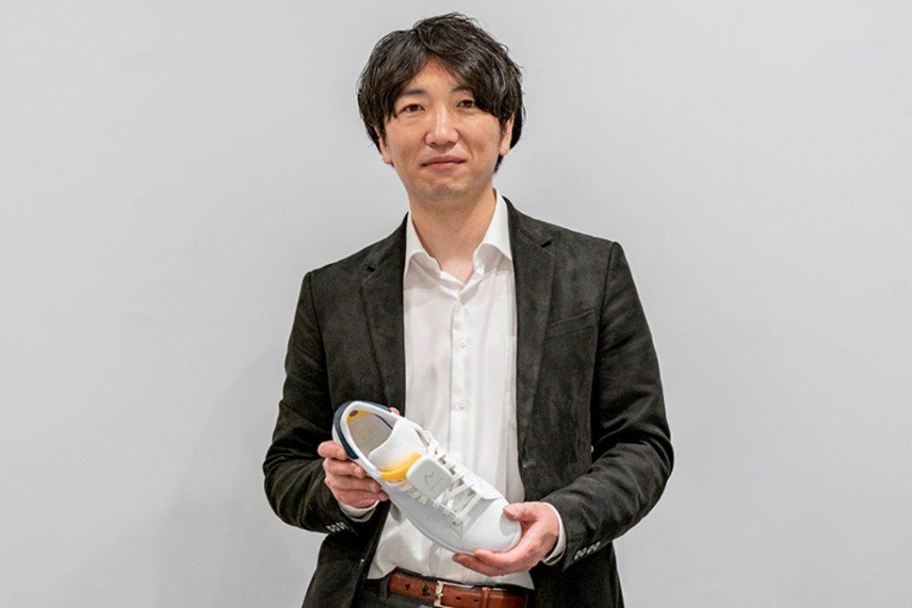 Fotografía de Wataru Chino, un joven empresario japonés que diseñó y desarrolló un sensor que se coloca en el calzado de las personas con discapacidad visual para guiarlos de manera segura. El hombre tiene el cabello negro, peinado con raya casi de lado, largo de enfrente y le cae sobre parte de un ojo y la frente. Sonríe. Viste camisa blanca y saco oscuro, abierto. En sus manos sostiene un tenis blanco que tiene adaptado el sensor.