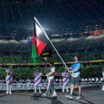 Momento en que un hombre desfila con la bandera de Afganistán en la ceremonia de apertura de los Juegos Paralímpicos de Tokyo 2020, aunque la delegación de dos atletas canceló su participación por la situación política en ese país. En la imagen, el abanderado vestido de gris y azul sostiene la bandera verde con rojo, entre una valla de voluntarios vestidos de blanco, que no se aprecian bien debido a la distancia de la foto.