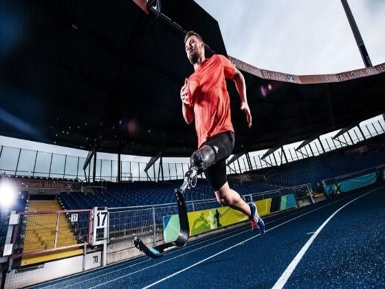 Fotografía de un paratleta en entretamiento, que viste ropa deportiva: camiseta anaranjada y short negro. Está en un estadio y la pista es azul con carriles blancos. El hombre joven en posición de correr tiene un dispositivo protésico en la pierna derecha, que está sujeto al muñón.  La imagen es cortesía de la empresa Ottobock.