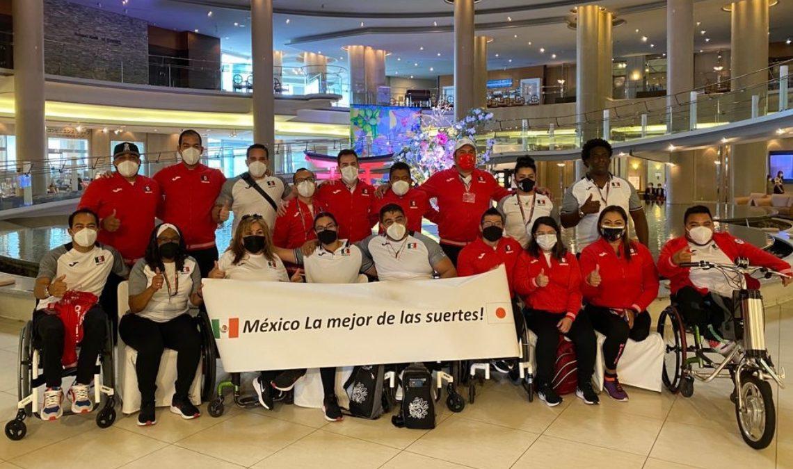"""Parte de la delegación mexicana que asiste a los Juegos Paralímpicos de Tokyo 2020. Son 18 personas colocados en dos filas, todos con el uniforme del equipo que consta de pants negros y chamarra roja. Todos usan cubrebocas y despliegan un letrero que dice """"México la mejor de las suertes"""", entre las banderas de México y Japón."""
