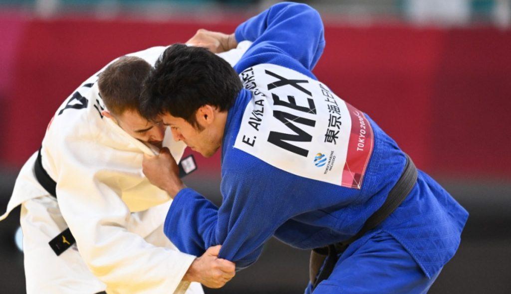 Fotografía que capta un momento del combate por la medalla de bronce en judo, del mexicano Eduardo Ávila. Tanto él como su oponente están semiagachados e inclinados, dando parte de su perfil a la cámara. El francés viste trabaje blanco y el mexicano azul. En las espaldas de su traje traen identificadores con sus nombres. Los dos usan cinta negra para abrochar el traje.