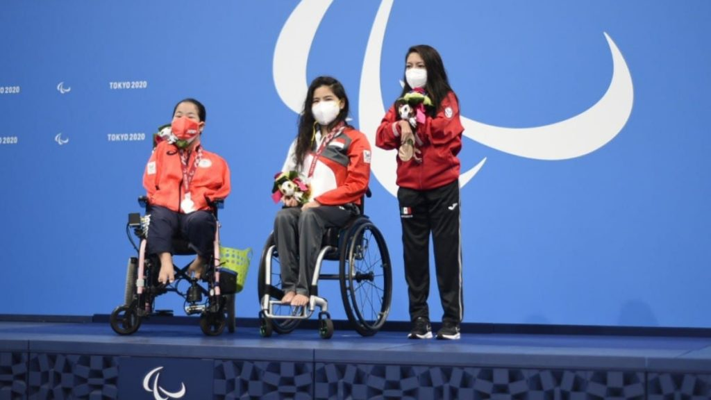 Fotografía del podio en el que Fabiola Ramírez, que está de pie, recibió la medalla de bronce en paranatación. En la imagen aparecen tres mujeres jóvenes; las primeras dos son usuarias de silla de ruedas. Todas lucen sus uniformes deportivos que coinciden en que son pant negros, con chamarras de color. Las de las deportistas en silla de ruedas son anaranjadas y la de Fabiola es roja. La tres usan cubrebocas. Detrás de ellas, en un fondo azul está el logo en blanco de los Juegos Paralímpicos de Tokio 2020.