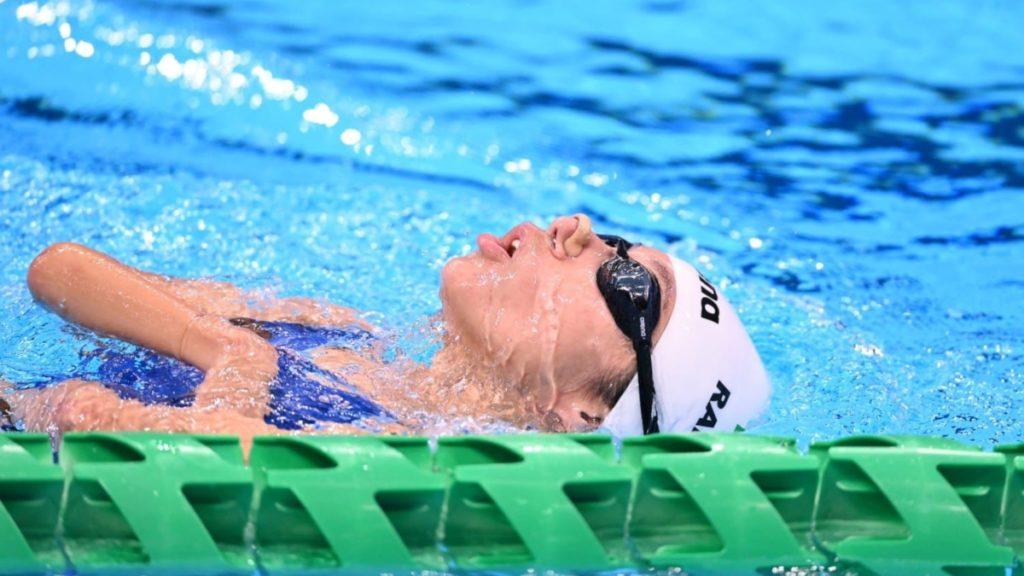 Fotografía de Fabiola Ramírez, nadadora mexicana que participa en los Juegos Paralímpicos de Tokio 2020. Ella nada en una alberca que luce azul por el efecto de los mosaicos con que está hecha, va pegada a un carril con protectores verdes. Nada de dorso, de tal manera que su cabeza está derecha y se ve de perfil, usa un gorro blanco y goggles negros.