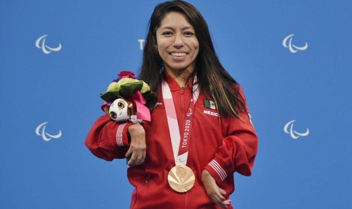 Fotografía de Fabiola Ramírez, nadadora paralímpica que ganó medalla de bronce en Tokio 2020. En la imagen viste el uniforme de México. Se ve su chamarra roja y en el pecho luce la medalla de bronce que recién le habían entregado por su triunfo. En el brazo izquierdo tiene el arreglo floral que entregan a los medallistas. Fabiola es una mujer de 31 años, de cabello largo, oscuro, lacio, que le cae sobre los hombros hacia adelante, y sonríe ampliamente.