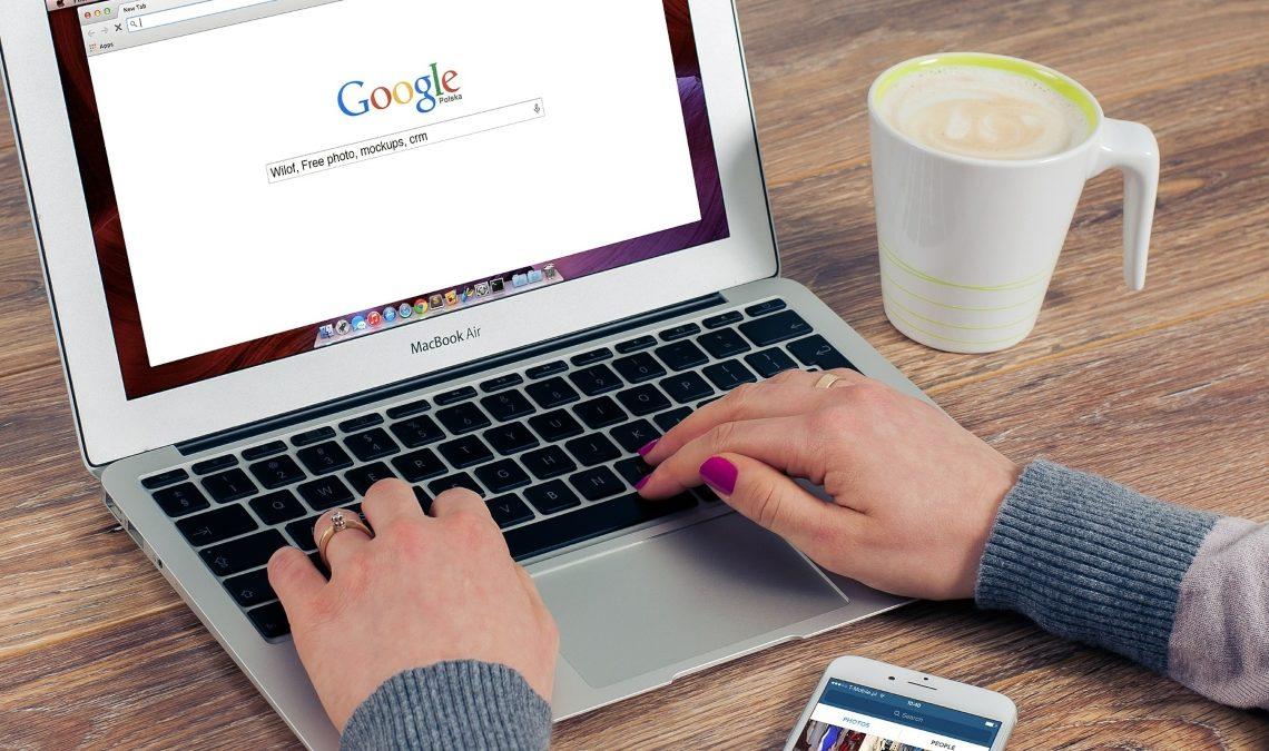 Fotografía en la que se ve una laptop abierta. En la pantalla está el buscador de Google. Sobre el teclado de la laptop hay un par de manos con uñas esmaltadas en rojo. Entre las manos, sobre la mesa, se aprecia parte de un celular y al lado derecho está una taza de café.