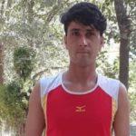 Fotografía del paratleta afgano Hossain Rasouli, de 24 años. Es un joven de cabello oscuro, abultado en el frente, que está parado frente a unos árboles. Se aprecia que viste la camiseta deportiva de su país, Afganistán, que es roja, sin mangan y la parte de los hombros es blanca. Tiene algunas líneas amarillas.