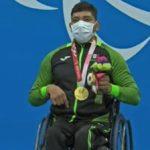 Fotografía de Jesús Hernández, nadador paralímpico que ganó la medalla de oro. En la imagen está sentado en su silla de ruedas, en el podio donde le entregaron la presea. Su silla de ruedas es negra, mismo color de los pants que usa y en el que destaca el color verde de las mangas de la chamarra. Es un hombre de 29 años, de cabello corto y negro, que usa un cubrebocas blanco. En su pecho luce la medalla de oro, y con la mano izquierda sostiene el arreglo de flores que le fue entregado como medallista. Atrás de él, en una pared azul está el emblema de los Juegos Paralímpicos de Tokyo 2020 en color blanco.