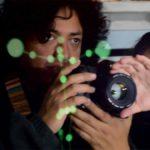 Fotografía de dos personas, un hombre y una mujer que sostienen entre sus manos una cámara fotográfica y preparan un encuadre, señalado con puntos en color verde que parten de lo ojos del hombre, de cabello largo, a los hombros, abundante y rizado. Ambos visten de negro y el rostro de la mujer no se percibe bien, ya que queda detrás de sus manos que manipulan la lente de la cámara.