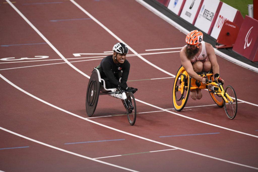 Fotografía de dos velocistas en silla de ruedas adaptadas que van muy parejos en la carrera, cada uno sobre uno de los carriles marcados en blanco en la pista de tartán.
