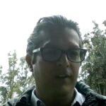Fotografía de Luis Quintana, un hombre joven, que usa lentes y lleva el cabello corto peinado hacia atrás.