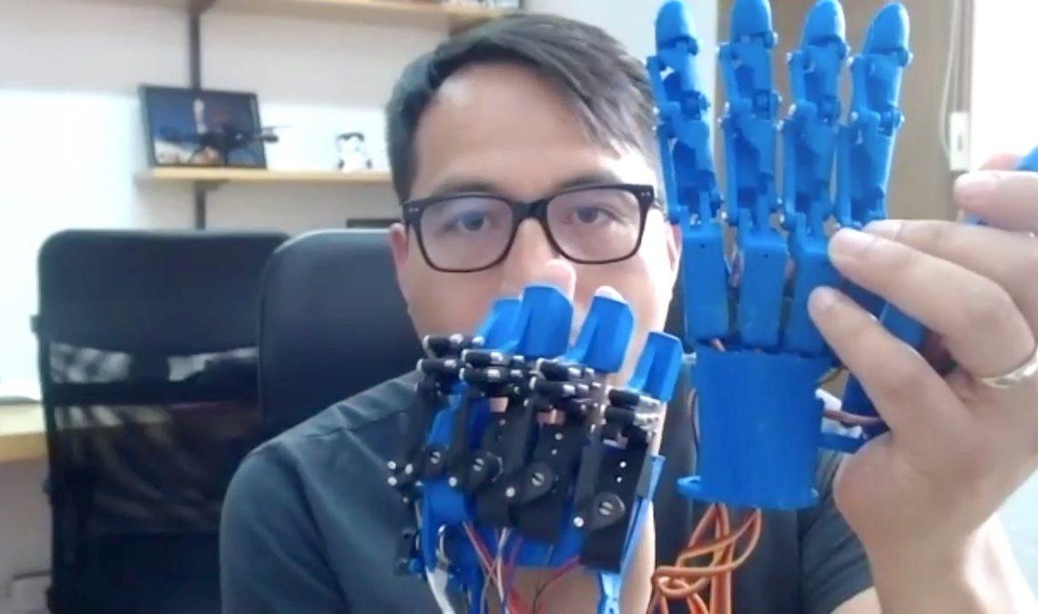 Fotografía de un hombre de unos 40 años o menos, con lentes de montura de pasta negra y cabello corto que le cae sobre la frente. Frente a él tiene dos manos robóticas en color azul que se activan y permiten el movimiento.