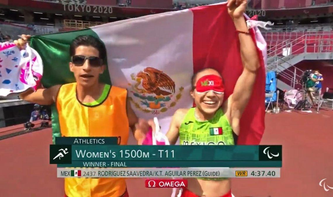 Fotografía de Mónica Rodríguez y su guía Kevin Aguilar después de ganar el oro en la prueba de 1500 m, categoría T11, en Tokio 2020. La imagen muestra a dos personas, un hombre y una mujer, celebrando, con la bandera de México a la espalda. Ambos visten uniformes deportivos de carrera atlética. En el de él sobresale un chaleco color amarillo naranja que es el distintivo de su condición de guía en la competencia; el de ella, es una camiseta corta, sin mangas, color verde, que deja ver el torso descubierto. Ella lleva unos shorts rojos, y sobre su rostro un antifaz color rojo. El guía usa lentes muy oscuros. Ambos son jóvenes, de figura espigada y sonríen.