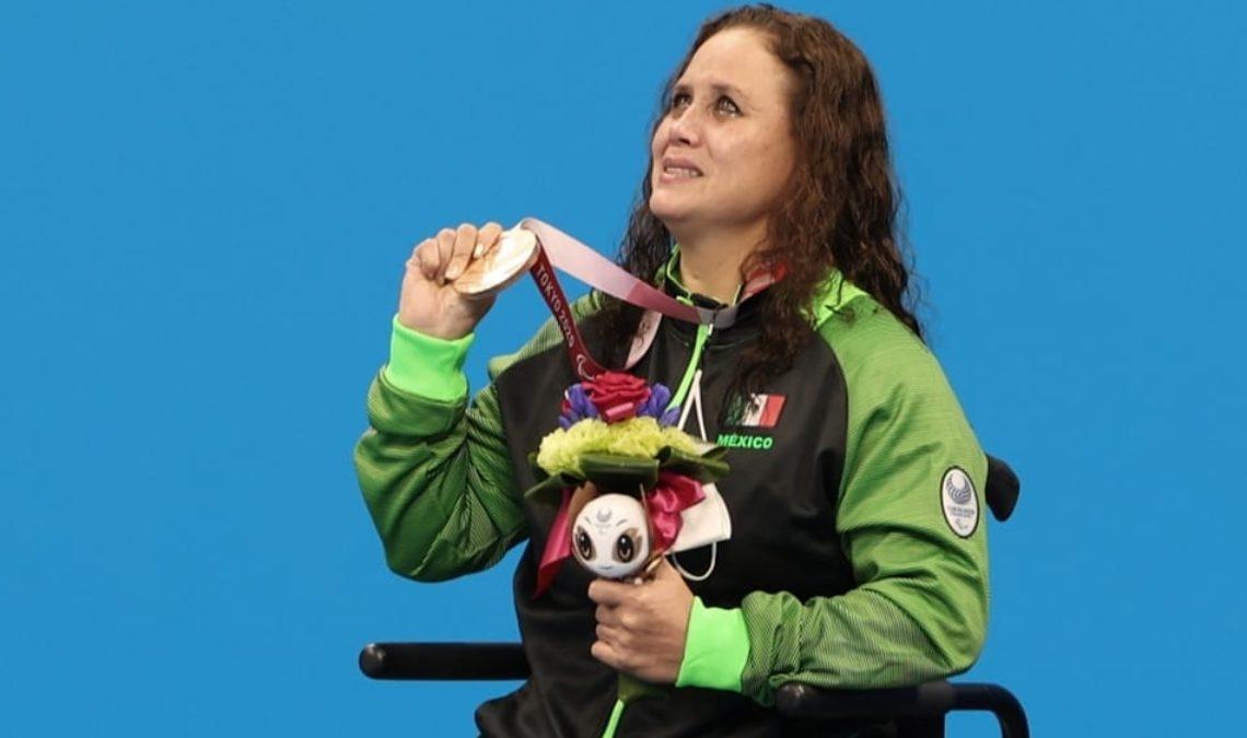 Fotografía de Nely Miranda, nadadora paralímpica. Ella es una mujer madura, usuaria de silla de ruedas. La fotografía tiene un encuadre de tres cuartos, que permite apreciarla cuando levanta y muestra la medalla que cuelga en su cuello con la mano derecha, mientras la izquierda permanece pegada a su cuerpo sosteniendo un ramo de flores. Ella tiene el cabello largo, semirrizado, teñido de color caoba, y viste el uniforme de la delegación mexicana, aunque solo es visible su chamarra negra con mangas verdes.
