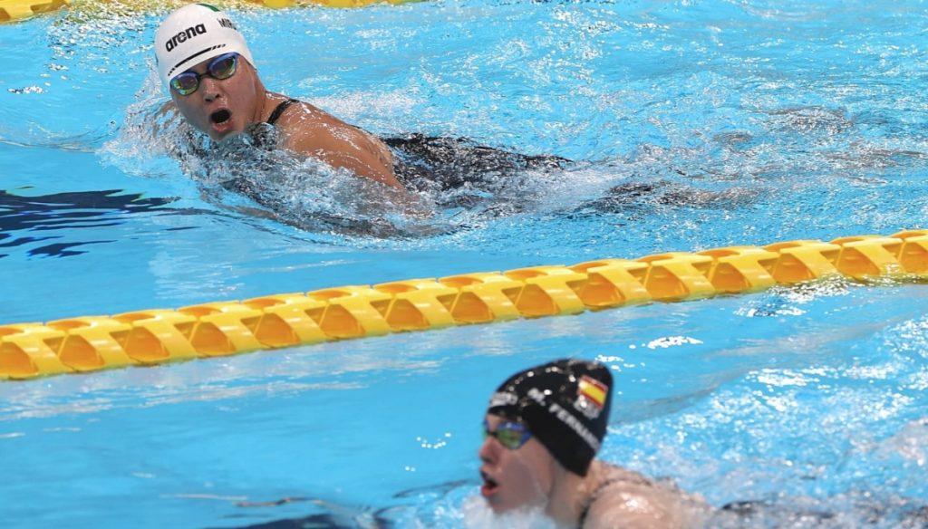 Fotografía de dos mujeres compitiendo en una prueba de natación, separadas por un carril en color amarillo. En la parte inferior, está una joven con goggles que usa un gorro plástico color negro con la bandera de España. En la parte superior, está Nely Miranda, con bañador en color negro, goggles y gorra blanca con la marca que la fabrica.