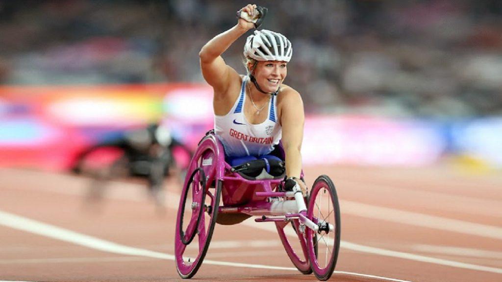 Fotografía de una paratleta en Río 2016 que compitió por Gran Bretaña en carreras en sillas de ruedas. Ella viste el uniforme deportivo británico en color blanco con azul; usa un gorro de protección color blanco y su silla es rosa. Tiene el brazo derecho levantado en señal de triunfo y sonríe.