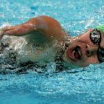 Fotografía de la sirena mexicana Patricia Valle, quien impuso un récord al participar en siete Juegos Paralímpicos. La imagen capta a la nadadora dentro de la alberca, con la cara de lado para respirar, tiene la boca abierta, goggles negros, y gorro de natación en dos colores: verde y rojo.