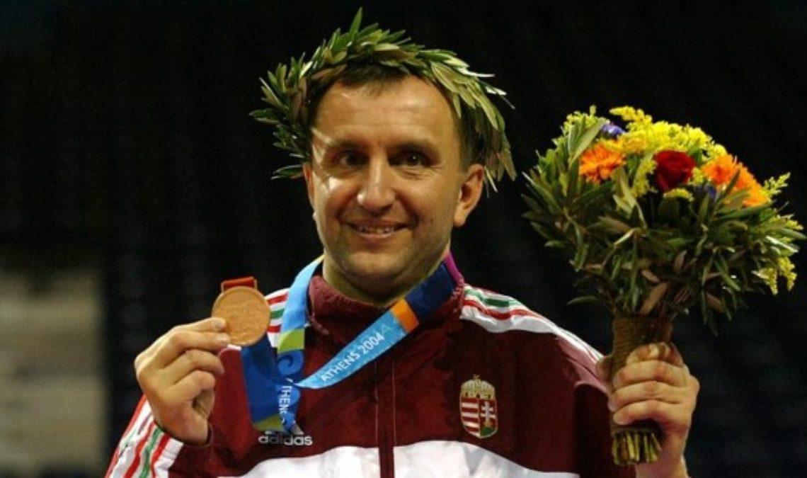 Fotografía del atleta húngaro Pál Szekers, único que ha ganado medalla olímpica y paralímpica. En la imagen se ve a un hombre de nariz recta y larga, rubio, que sonríe tras recibir una de las medallas que ganó, y a la que muestra levantándola con la mano derecha. En la cabeza tiene una corona de laurel en señal de victoria, y en la izquierda un ramo de flores.