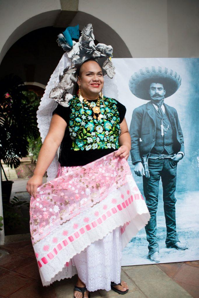 Fotografía de Pedro Edgardo Miranda, un hombre de edad adulta, cuerpo robusto y cara ancha que aparece vestido de un traje típico, falda blanca con flores de color rosa bordadas, playera negra con flores de color verde agua, y un sombrero de color gris y un velo de color blanco, aparece sonriente frente a la cámara.