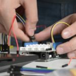 Prototipo del dispositivo de asistencia que traduce textos en Sistema Braille a audio diseñado por estudiantes del Tec de Monterrey. En la fotografía se ven unas manos, ante una especie de teclado blanco, más pequeño que una de las manos, al que están conectados unos cables.