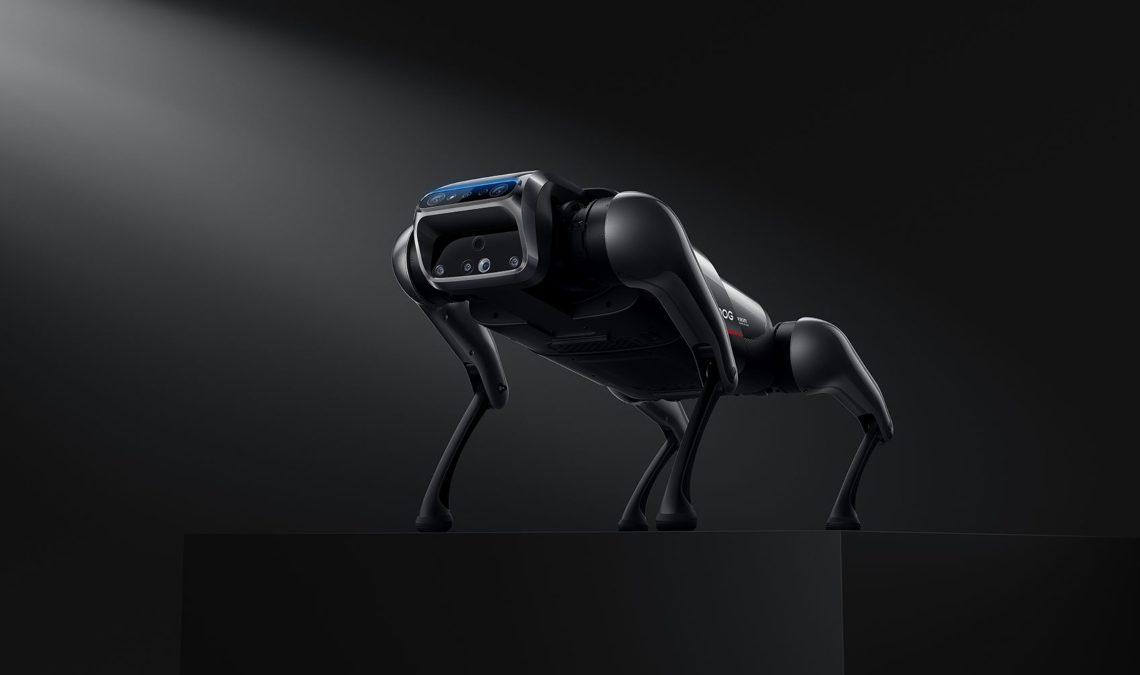 Fotografía muy contrastada en tonos de negros y grises que muestra al perro robot de Xiaomi; se trata de un robot que semeja a un perro musculoso y que en un cabeza tiene una pantalla, que vista de manera rápida semeja a una escafandra de buzo.