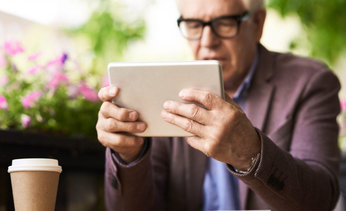 Fotografía de un adulto mayor sosteniendo una tableta de color blanca frente a su rostro, la tableta y sus manos un poco arrugadas de tez blanca que están en primer plano, su rostro se encuentra en segundo plano y difuminado, con cabello cano y lentes con armazón de color negro, saco de color café con camisa de color azul marino.