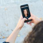 """Fotografía en donde aparece el reflejo de una mujer en la pantalla de un teléfono móvil que dice """"Scan"""", el teléfono escanea el rostro de la mujer, quien sostiene el móvil con ambas manos; se aprecia que la mujer de edad media tiene cabello castaño oscuro con rizos cerrados y mucho volumen, su tez es morena y tiene ojos de color café."""