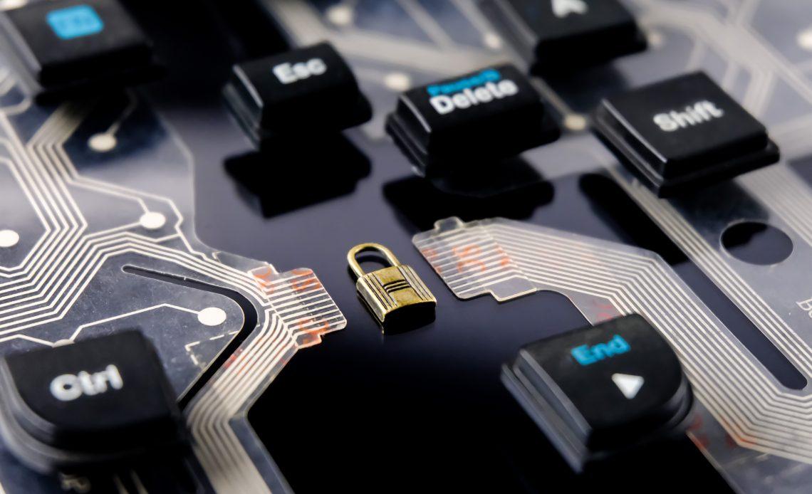 """Fotografía del sistema operativo """"hadware"""" de una computadora, se alcanza a apreciar una especie de tarjeta madre de color negro con algunas teclas al rededor: delete, shift, ctrl y end, en medio de todo se encuentra un candado de color dorado cerrado, entre los enlaces de la tarjeta."""