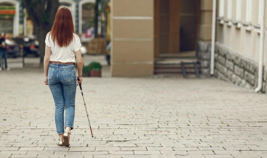 Fotografía de una mujer joven de cabello rojizo, que lleva puesto un pantalón de mezclilla azul y una blusa color beige; se encuentra caminando por una acera, va apoyada por un bastón guía para personas con discapacidad visual.