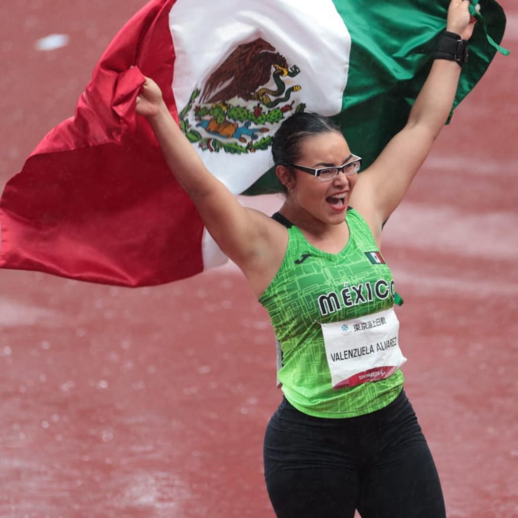 Fotografía de Rebeca Valenzuela, una mujer de mediana edad, cuerpo robusto que viste pantalón negro y camisa deportiva de color verde, se encuentra ondeando una bandera de México con ambos brazos.