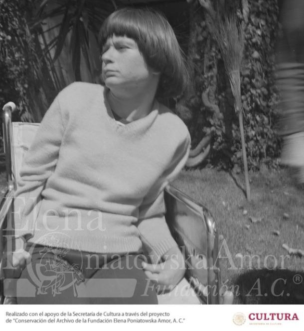 Fotografía en blanco y negro de Gaby Brimmer, en una etapa de juventud. Es una joven con parálisis cerebral, usuaria de silla de ruedas, Aunque la imagen es de frente, ella voltea sobre su hombro derecho. Usa un suéter claro y pantalón oscuro. Tiene el cabello lacio, cortado en forma de hongo, con fleco tupido. Su nariz es larga y recta.  La silla de ruedas está en un jardín.