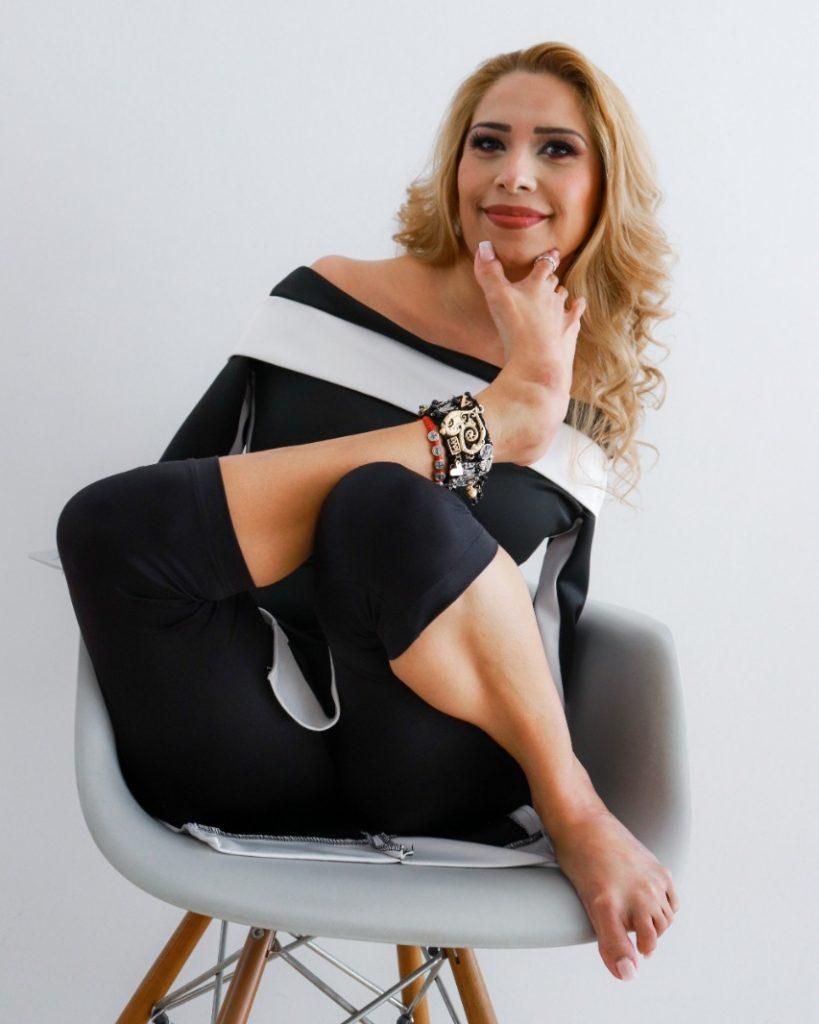Fotografía de Adriana Macías, una mujer joven, de cabello teñido de rubio, a la altura del hombro, con rizos en las puntas. Está sentada sobre una silla gris. Viste un traje negro, son una aplicación blanca que deja los hombros desnudos. No tiene brazos. Su pierna izquierda está doblada sobre la silla; la pierna derecha la recarga sobre la rodilla izquierda y con su pie toma la barbilla, abriendo los dedos pulgar e índice en forma de V. En el tobillo lleva varias pulseras y en el dedo índice una argolla. Las uñas de sus pies son largas, con manicura y esmalte blanco.