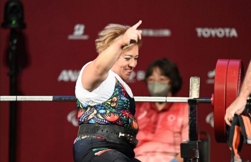 Imagen de una mujer de mediana edad, robusta, de tez morena clara, cabello teñido de rubio, está de perfil frente unas pesas con barras plateada y discos color rojos. Sonríe mucho y levanta su brazo y dedo índice.