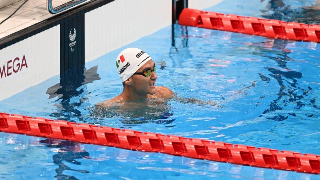 Fotografía del nadador José de Jesús Camacho, un deportista muy joven, que está flotando en la alberca después de la competencia. Está en medio de dos carriles rojos. Solo la cabeza sobresale del agua. Usa gorra blanca, con la bandera de México al costado. También tiene goggles color tornasol.