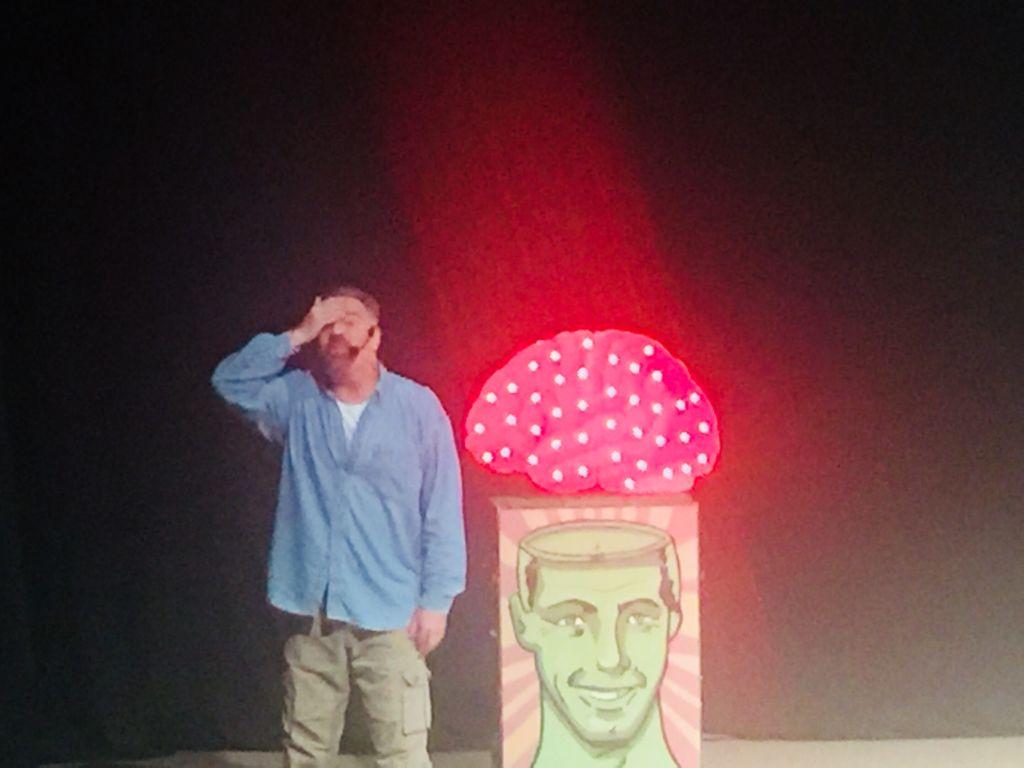 """Fotografía de Ari Telch en plena actuación, en un escenario oscuro, iluminado con luz cenital para enfocar a un enorme cerebro rojo con puntos blancos que está sobre una especie de caja con la imagen de un hombre, con la cabeza """"destapada"""" lo que permite que el cerebro salga. Aunque el actor está en primer plano, llama más la atención la figura del cerebro.  El actor viste pantalón color caqui, flojo, y camisa azul clara, de manga larga, desabotonada al frente, lo que deja ver una camiseta blanca. El actor se lleva la mano derecha a la frente, y sobre su cabeza se ve la diadema del micrófono inalámbrica que usa."""