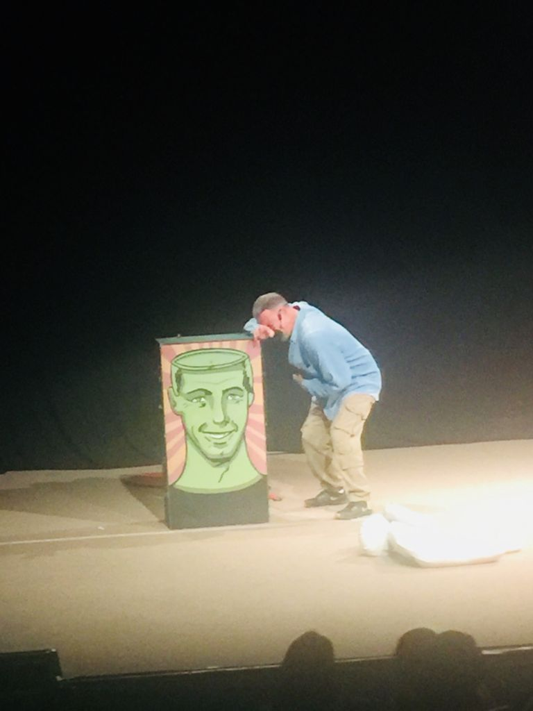 Escena del actor Ari Telch, quien viste pantalón color caqui y camisa azul de manga larga, de lado, inclinado y en actitud de llanto o risa, recarga su cabeza sobre su mano derecha, que está en la parte superior de la caja que muestra la cara de un hombre verde, con la cabeza abierta.