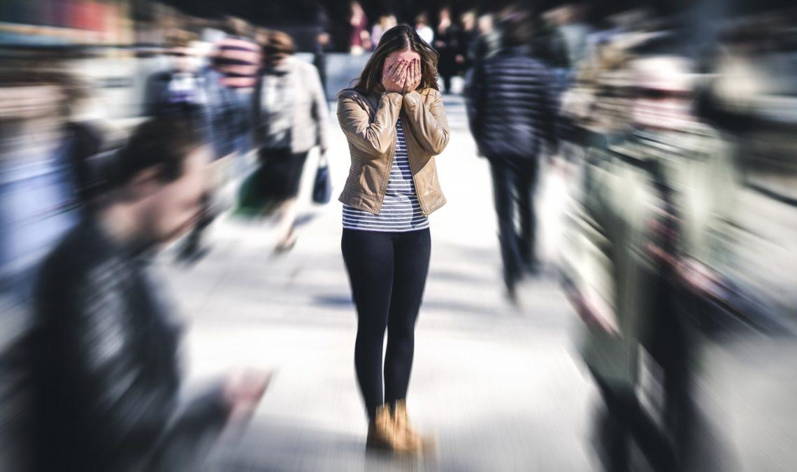 Fotografía de una mujer en la calle en medio de personas cuyas imágenes se ven difuminadas. La mujer es joven, viste pantalón negro, playera azul clara cubierta con una chamarra color beige, abierta. Tiene el café oscuro y cubre su rostro al llevarse las manos hacia él.