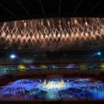 Fotografía de un aspecto de la clausura de los juegos paralímpicos de tokio 2020, abajo se ve una mancha azul conformada por los atletas que están en la cancha y rodean un espacio brillante en tonos blancos y amarillos, en la parte superior se aprecian cientos de luces, como juegos pirotécnicos que iluminan la noche oscura.