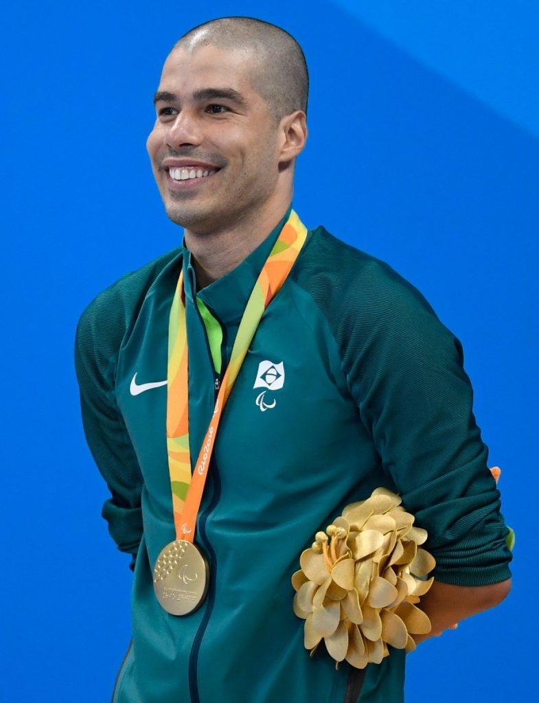 Fotografía de Daniel Dias, el campeón paralímpico de Brasil, en uno de los muchos podios que subió en su vida. En la imagen se le ve sonriente, con unos pants deportivos turquesa y una medalla colgando sobre su pecho de un listón anaranjado y verde. Él es un hombre joven que lleva la cabeza rapada y solo se le ve como una especie de sombra, en vez de cabello.