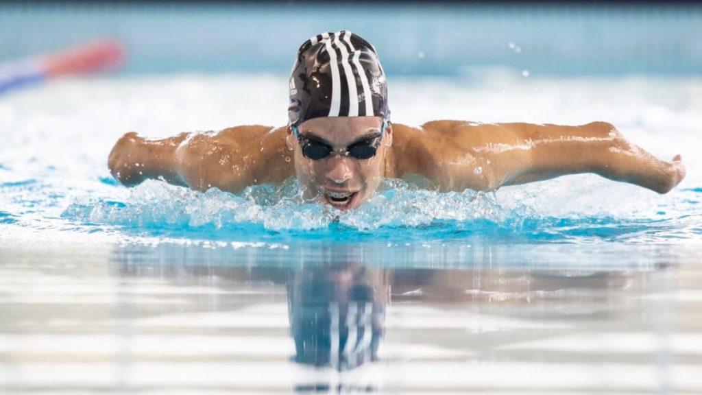 Imagen de un deportista en una prueba de nado de mariposa, los brazos van hacia atrás y él va rompiendo el agua, creando ondas. Usa una gorra negra con tres franjas verticales blancas y goggles negros.