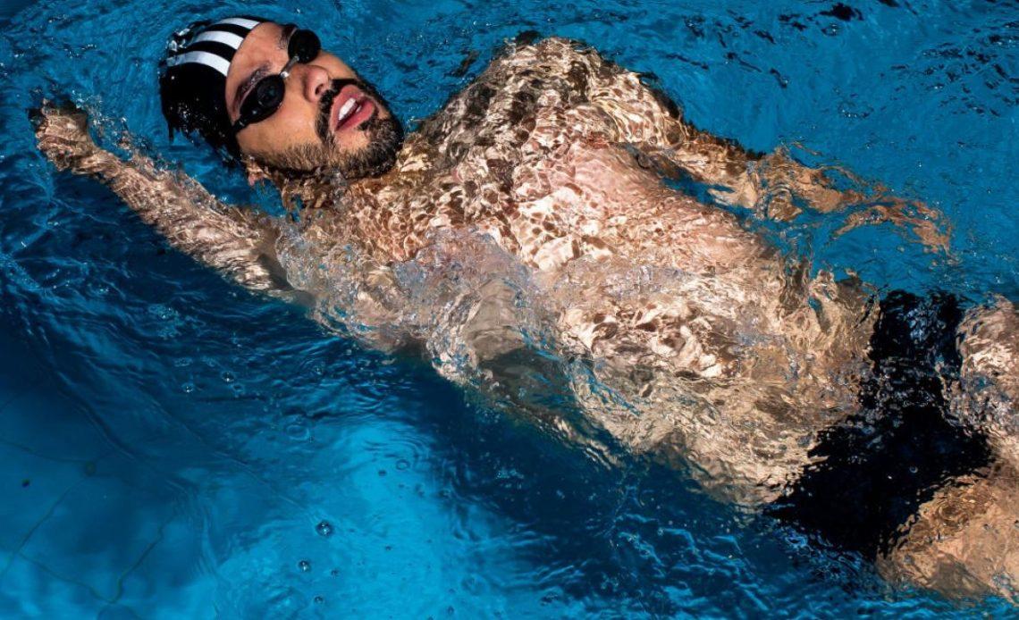 Fotografía de Daniel nadando de dorso. Lleva barba y bigote negros, goggles negros y un gorro negro con francas verticales blancas.