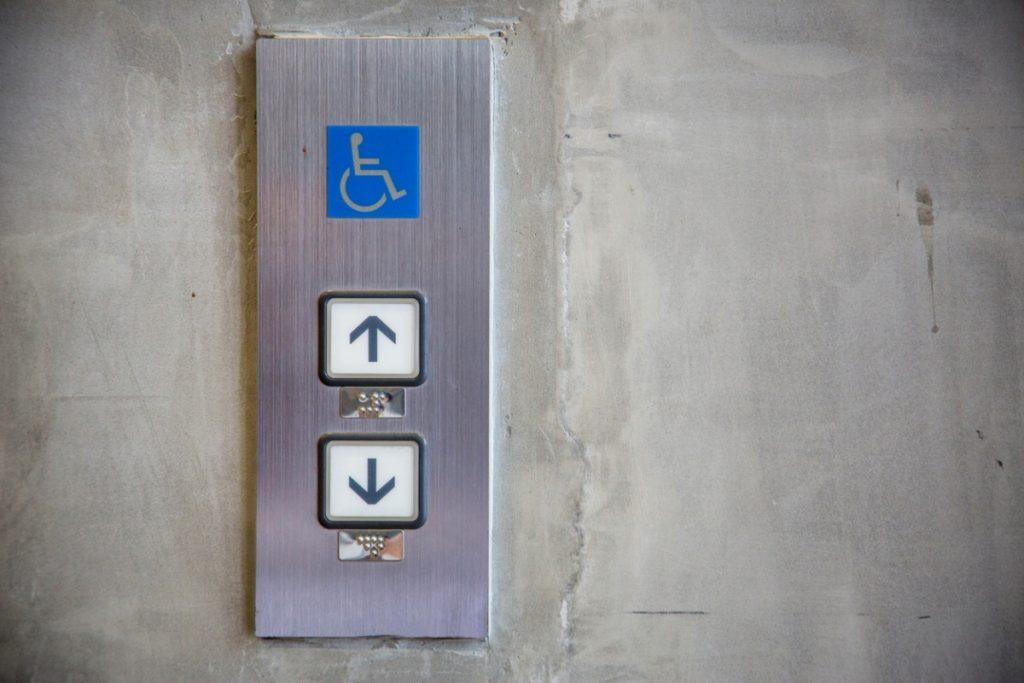 Acercamiento a la señalización de un elevador que está colocado en una pared de concreto. Se trata de una placa de metal, de forma rectangular que tiene cinco gráficos: de arriba hacia abajo aparece en un cuadrado azul el icono universal de la discapacidad motriz (una silla de ruedas con la silueta de un usuario); sigue un recuadro blanco donde aparece una flecha que indica hacia arriba y abajo está su representación  en braille en una pequeña lámina rectangular; posteriormente, en otro cuadro blanco está una fecha gris que indica hacia abajo seguida de su representación en braille.
