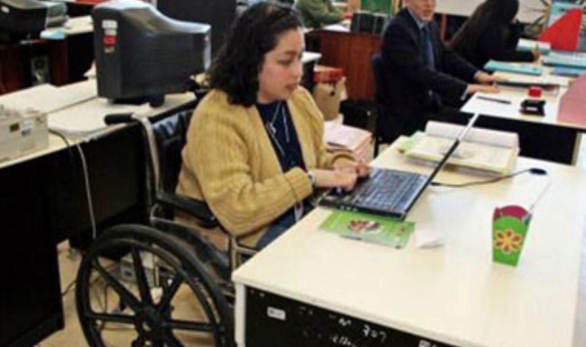 Fotografía de una mujer usuaria de silla de ruedas en un ambiente laboral en el que se ven varias líneas de escritorios. Ella es una mujer entre 30 y 40 años, de complexión robusta, con cabello negro, al hombro, usa blusa negra y suéter beige, está frente a una laptop abierta y sus manos están colocadas sobre el teclado.