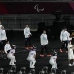 Fotografía oscura en la que desfila un grupo de atletas con discapacidad que forman la delegación de refugiados que compite en Tokyo 2020. La imagen capta un momento de su participación en el desfile inaugural. El equipo de refugiados viste pantalón negro y saco blanco, mientras camina entre un grupo de voluntarios vestidos de blanco que están casi en cuchillas. La imagen fue tomada a gran distancia y no permite distinguir los detalles de cada persona; solo se ven sus siluetas.