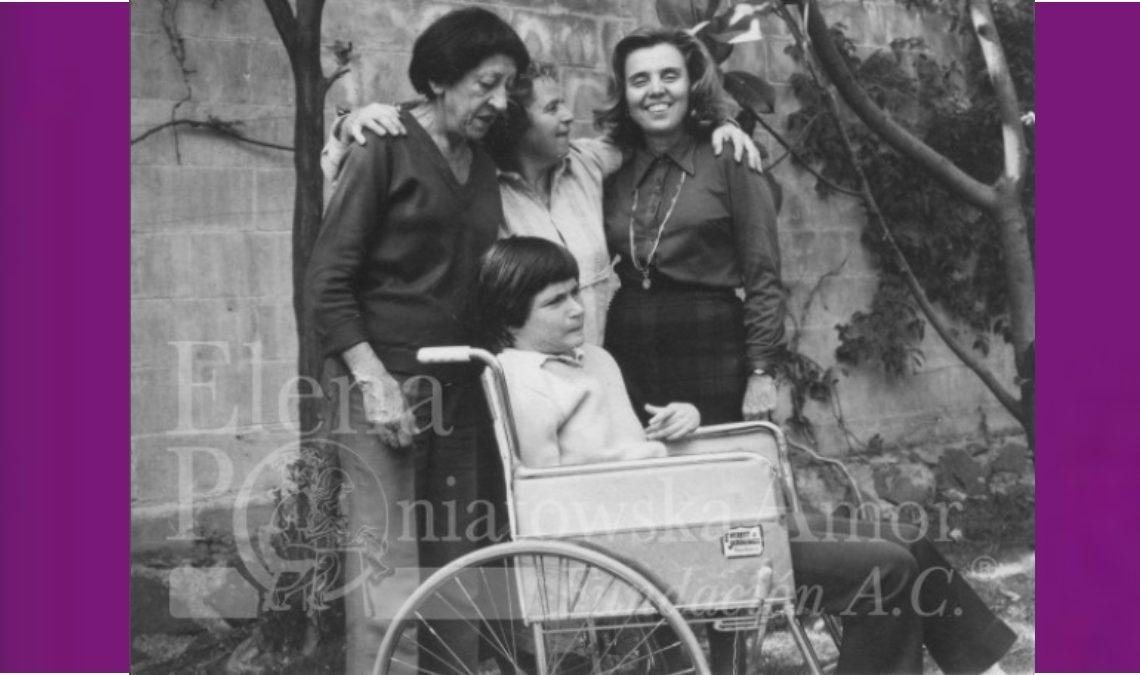 Fotografía en blanco y negro de cuatro mujeres, tres de ellas están de pie y la que está en medio abraza a las otras dos. Enfrente de ellas está una jovencita en silla de ruedas que usa un vestido claro, que contrasta con la ropa oscura de las mujeres de pie.