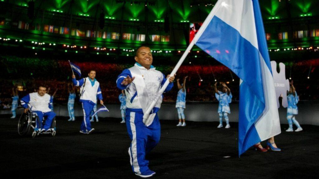 Imagen de un hombre de talla baja que porta la bandera de su país, El Salvador, que tiene colores azul y blanco, al igual que los trajes deportivos que visten él y compañeros que le siguen a bastante distancia. El joven de tez morena y rapado sostiene el asta bandera con la mano izquierda y, con la derecha saluda mientras sonríe.